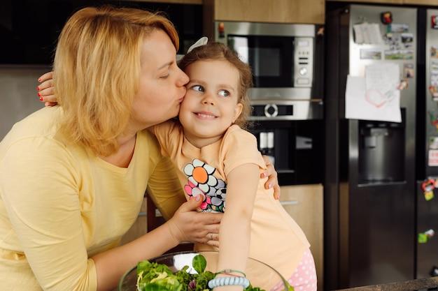 Maman embrasse et embrasse sa fille de 3 ans sur la joue. concept de relation maman et fille. psychologie de la famille et de l'enfant. gros plan portrait.