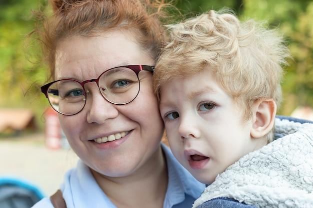 Maman embrasse un enfant handicapé, regarde la caméra et sourit.