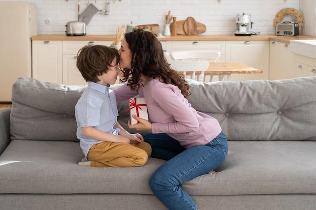 Maman embrasse l'enfant reçoit une boîte cadeau emballée avec un arc rouge