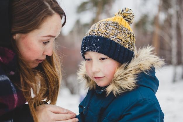 Maman embrasse et réchauffe les mains de son petit fils, marche dans le parc d'hiver, marche, mains froides et glaciales