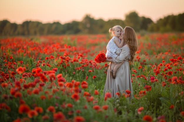 Maman embrasse sa fille dans un champ de pavot en été