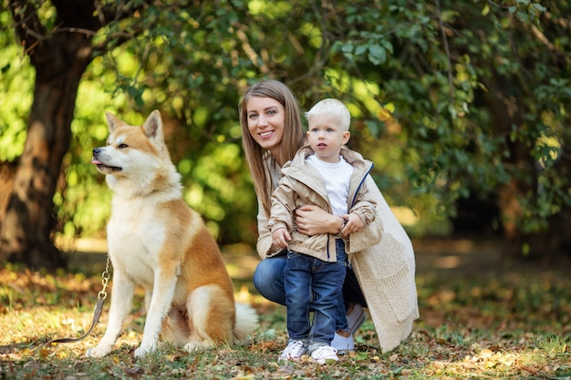 Maman embrasse son fils près du chien rouge dans le parc de l'automne