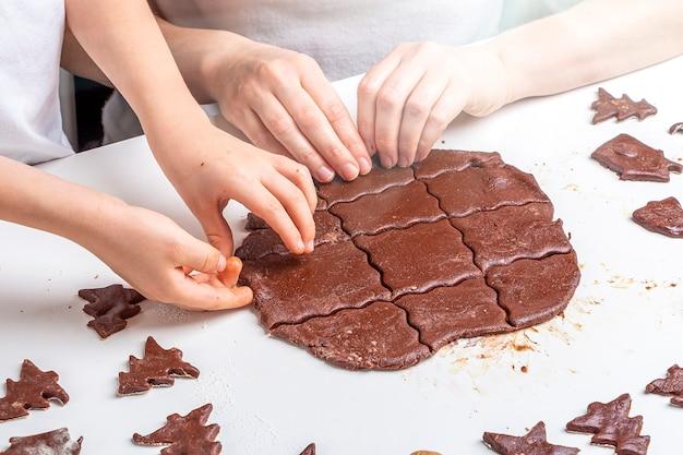 Maman et enfant découpent la pâte avec des moules pour les biscuits