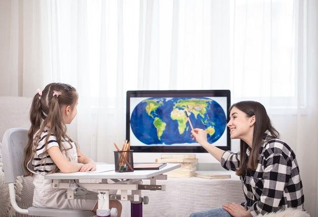 Maman et enfant font leurs devoirs avec la géographie à l'aide d'une carte. concept d'enseignement et d'éducation à domicile.