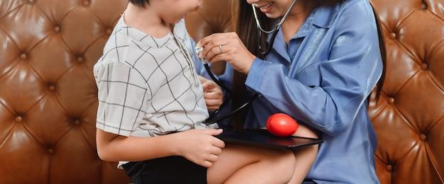 Maman et enfant jouant ensemble en tant que médecin dans le salon. mode de vie et activité familiale. une mère asiatique travaille à la maison avec son fils.