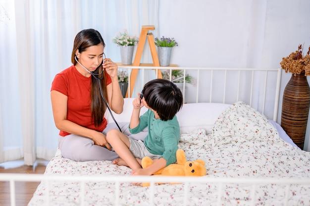 Maman et enfant jouant ensemble en tant que médecin sur le lit. mode de vie de la femme et activité familiale. une mère asiatique travaille à la maison avec son fils.