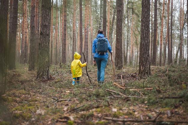 Maman et enfant marchant dans la forêt après la pluie dans des imperméables avec des bâtons de bois dans les mains, vue arrière