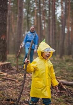 Maman et enfant marchant dans la forêt après la pluie dans des imperméables avec des bâtons en bois dans les mains