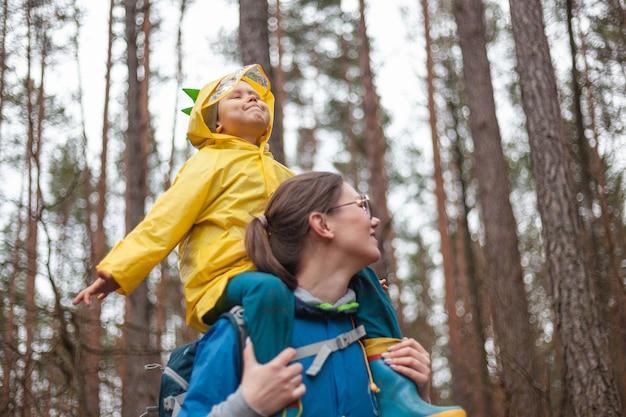 Maman et enfant marchant dans la forêt après la pluie dans des imperméables ensemble, l'enfant est assis sur les épaules de maman, regardant joyeusement le ciel