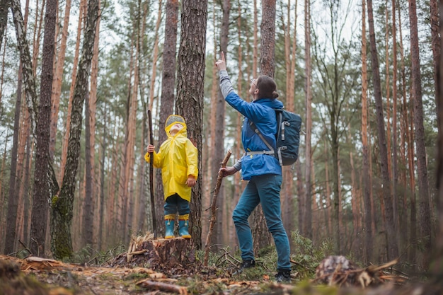 Maman et enfant marchant dans la forêt après la pluie dans des imperméables ensemble, regardant le ciel
