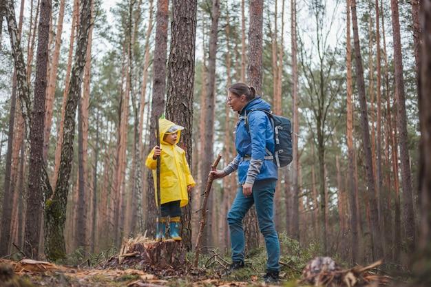 Maman et enfant marchant dans la forêt après la pluie dans des imperméables ensemble