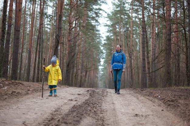 Maman et enfant marchent ensemble sur la route forestière après la pluie en imperméable