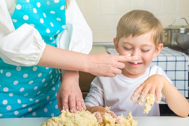 Maman et enfant pétrissent la pâte