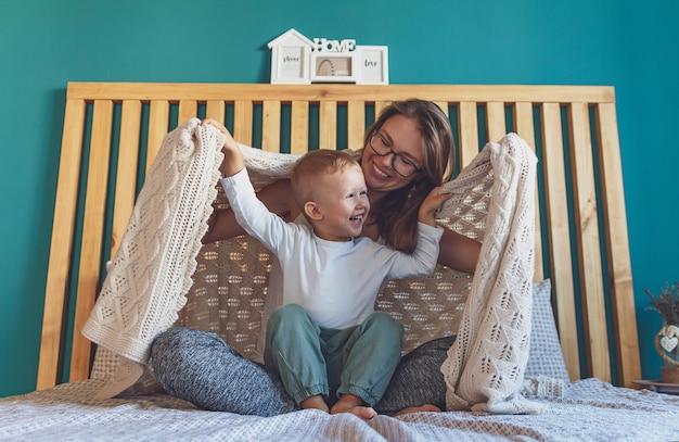Maman et enfant s'amusent dans la chambre sur le lit sous le blanc