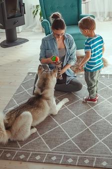 Maman et enfant s'amusent et jouent avec un chien à la maison