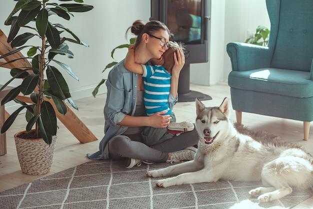 Maman et enfant s'amusent et jouent avec le chien à la maison