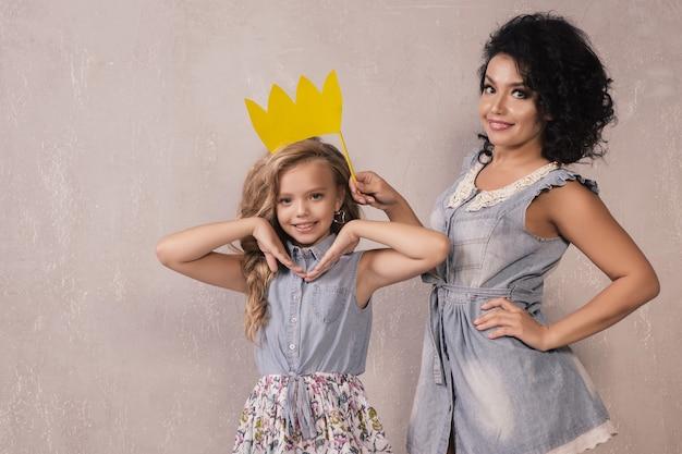 Maman et enfant tiennent une couronne de papier sur un bâton
