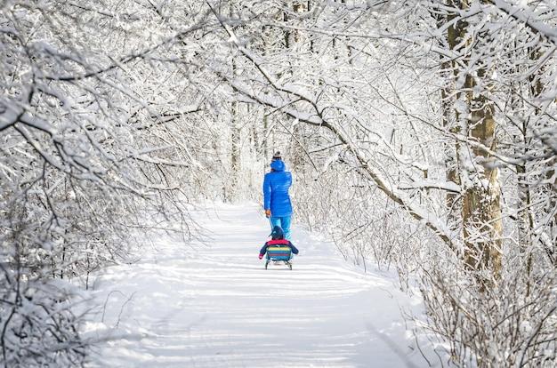Maman et enfant sur un traîneau sur un chemin d'hiver dans une forêt enneigée.