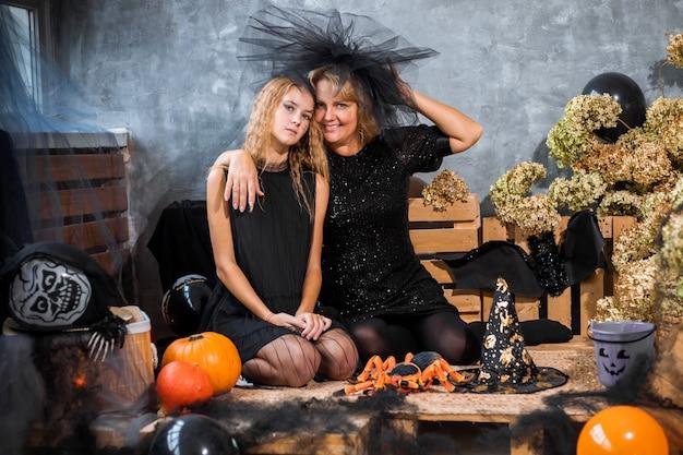 Maman avec enfants fille fille 12 ans parmi décor aux tons orange et noir pour halloween s'amuser et passer du temps ensemble