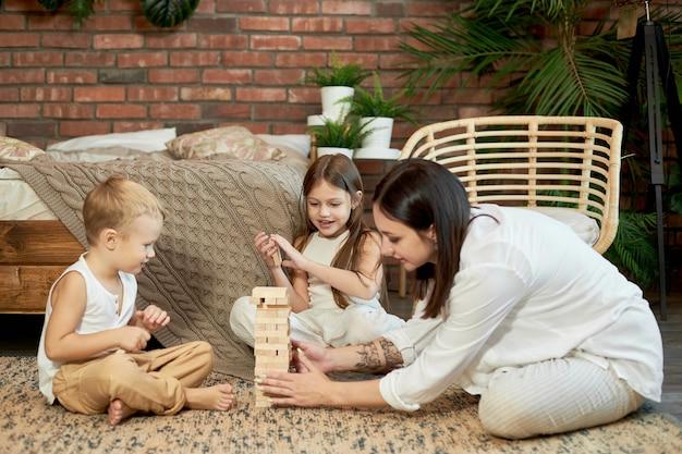 Maman et les enfants jouent à la tour de jenga de squirl. femme fille et garçon jouent au jeu de puzzle familial. journée en famille