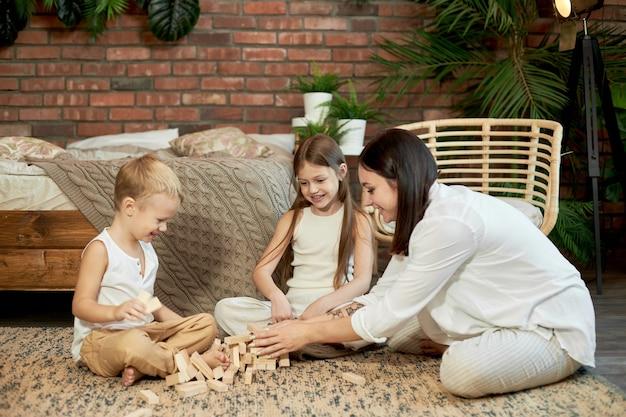 Maman et les enfants jouent à la tour de squirl. femme fille et garçon jouent au jeu de puzzle familial. journée en famille