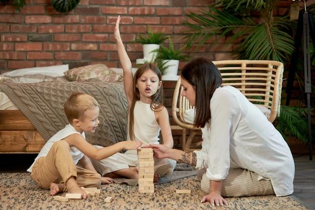 Maman et les enfants jouent à la tour de squirl. femme fille et garçon jouent au jeu de puzzle familial