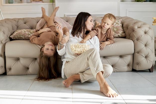 Maman et enfants mangent du pop-corn à la maison un jour de congé