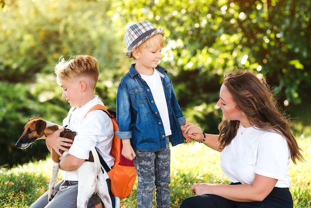 Maman et enfants s'amusant à jouer avec un chien à l'extérieur. héhé, profitant du parc par beau temps. petit chiot jack russel terrier marchant avec les propriétaires. les enfants et le chien sont les meilleurs amis.