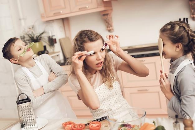 Maman et enfants s'amusent dans la cuisine avec des légumes