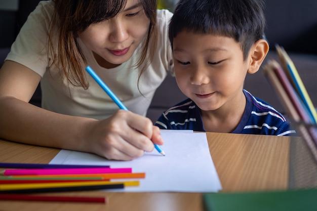 Maman enseigne les devoirs à son fils dans le salon de la maison. le parent et l'enfant partenaire passent un moment heureux et détendu lorsqu'ils font leurs devoirs, construisent une relation dans la famille.