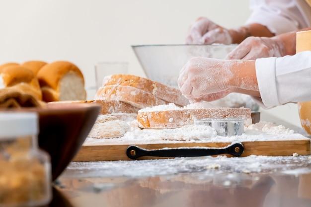 Maman enseigne à l'enfant à cuisiner. préparation d'un ingrédient avec de la poudre et du pain.