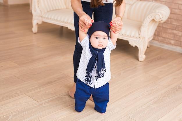 Maman enseigne les premiers pas de son fils à l'intérieur.