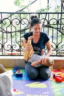 Maman est assise sur le balcon tenant une petite fille sur ses genoux
