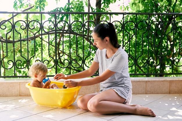 Maman est assise par terre à côté d'une petite fille dans un bassin sur le balcon