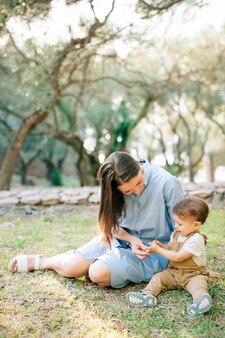 Maman est assise avec son petit fils dans l'herbe dans une oliveraie et joue avec lui