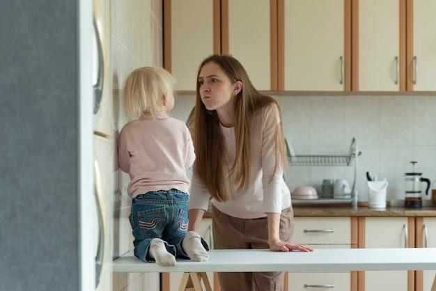 Maman est en colère contre le petit enfant debout dans la cuisine.
