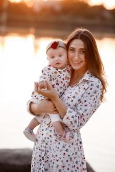 Maman étreignant sa fille et s'amusant près du lac au coucher du soleil. le concept de vacances d'été. fête des mères, du bébé. famille passant du temps ensemble sur la nature. look familial. mise au point sélective