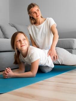 Maman avec exercice d'entraînement de résistance d'entraînement de fille