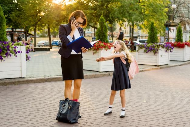 Maman femme d'affaires prend l'enfant à l'école