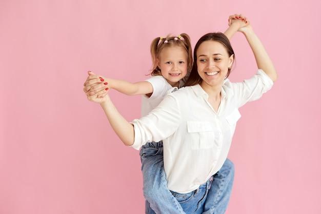 Maman femme en vêtements légers s'amuse avec une jolie petite fille. petite fille assise sur le dos de la mère isolée sur fond rose pastel. portrait en studio.