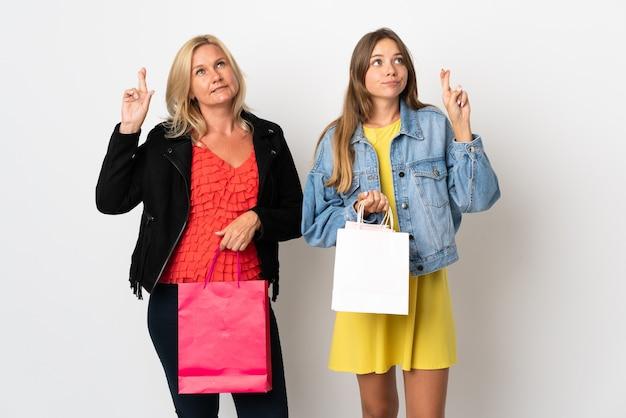 Maman et fille achetant des vêtements isolés sur un mur blanc avec des doigts croisés et souhaitant le meilleur