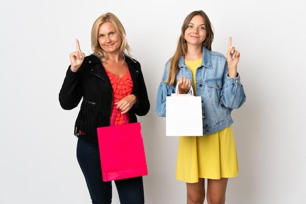 Maman et fille d'acheter des vêtements isolés sur un mur blanc montrant et en levant un doigt en signe de la meilleure