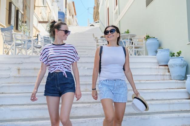 Maman et fille adolescente marchant parler ensemble