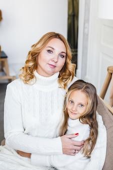 Maman et fille assise sur le canapé parent étreint l'enfant