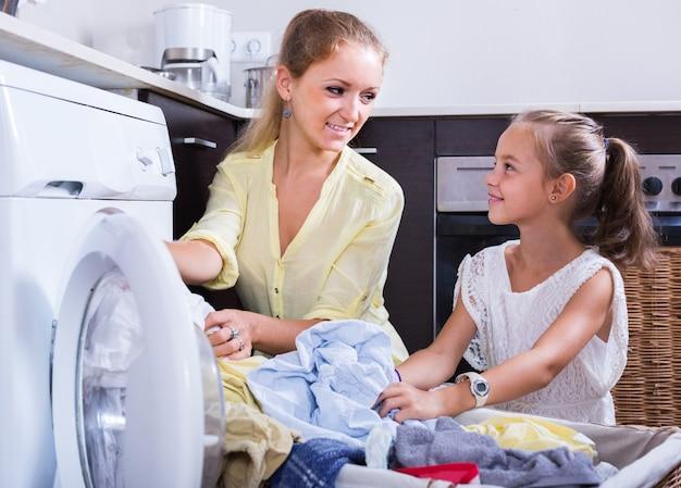 Maman et fille avec bin près de la machine à laver