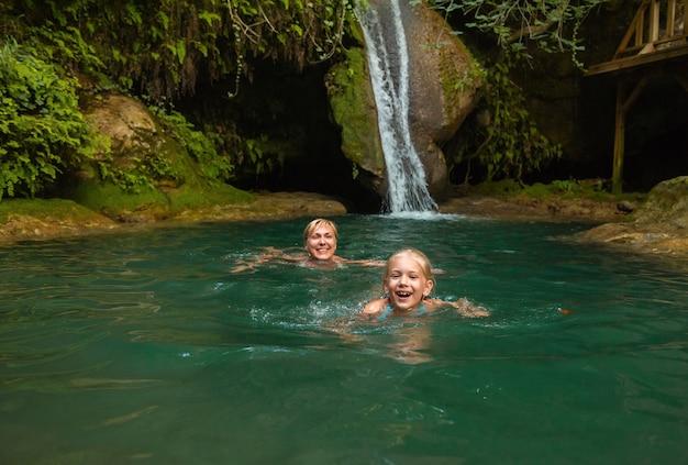 Maman et fille à une cascade dans la jungle. voyagez dans la nature près d'une belle cascade, turquie.