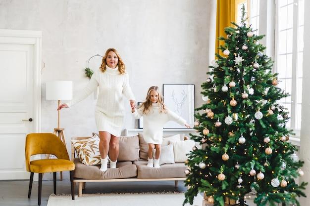 Maman fille cheveux blonds habillés chandails légers, vacances d'attente, salle décorée célébrer noël, canapé sautant, jeux pour enfants amusants