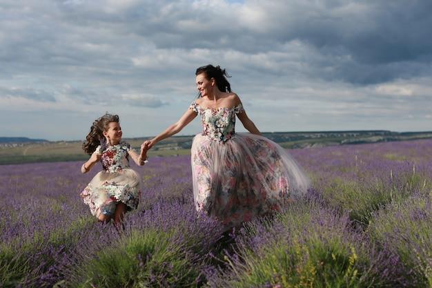 Maman et fille courent dans un champ de lavande