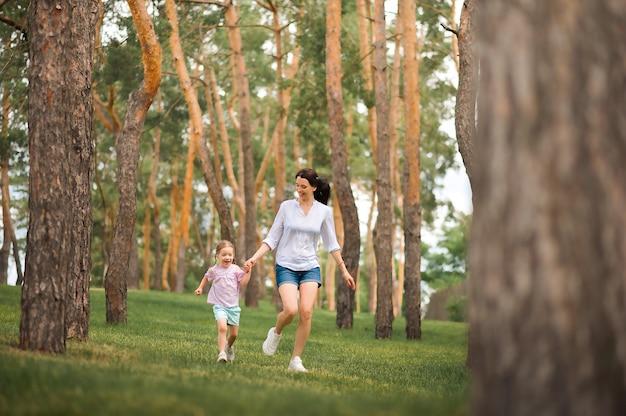 Maman et fille courent dans le gros plan de la forêt