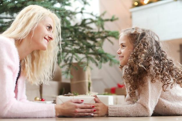 Maman et fille dans le salon décoré de noël